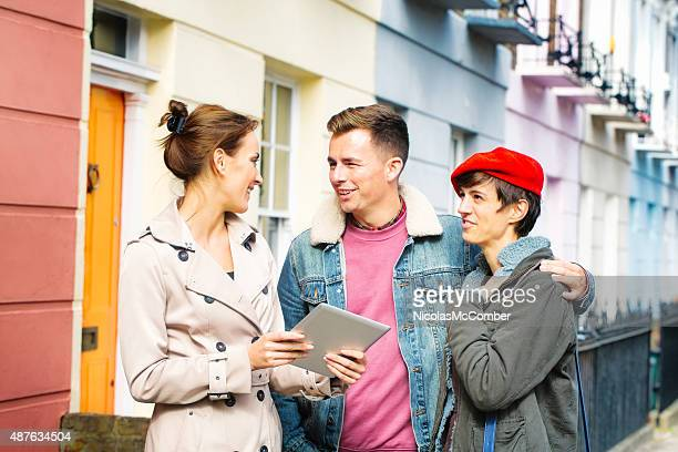 Young British couple discussing real estate with female agent outdoors