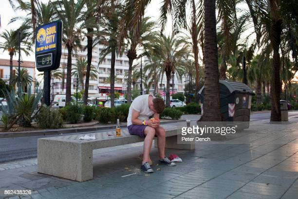 A young British man cluthches a packet of chips as the sun rises over the West End area of San Anronio Ibiza