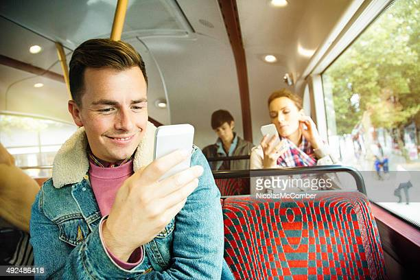 Young British people using their phones on London bus ride
