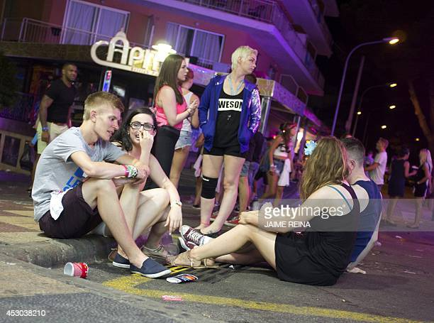 Young British tourists chat in Punta Ballena street as they have fun in the Magalluf zone in Calvia on Mallorca Island late on August 1 2014 The...