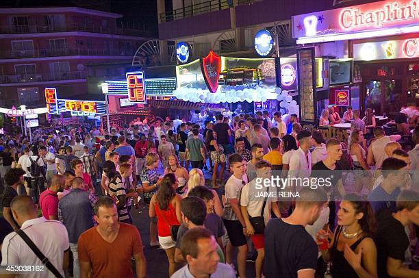 Young British tourists walk down Punta Ballena street as they have fun in the Magalluf zone in Calvia on Mallorca Island late on August 1 2014 The...