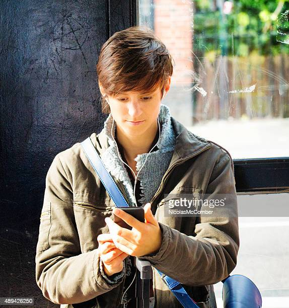 Young British woman waiting for bus phone in hand