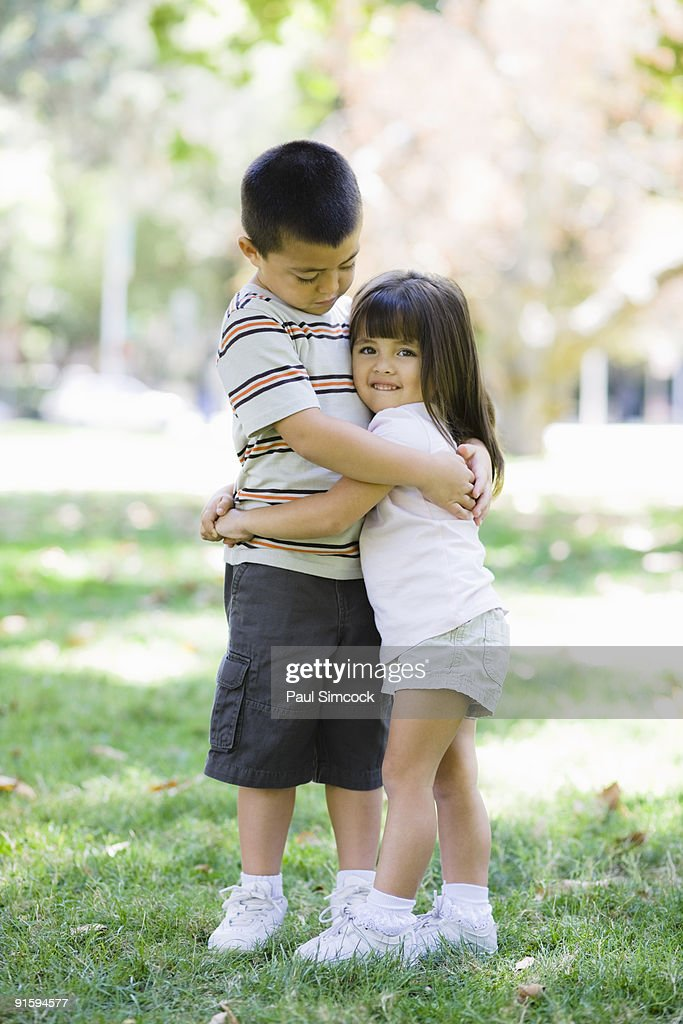 Young Brother and Sister Hugging In Park : Stock Photo
