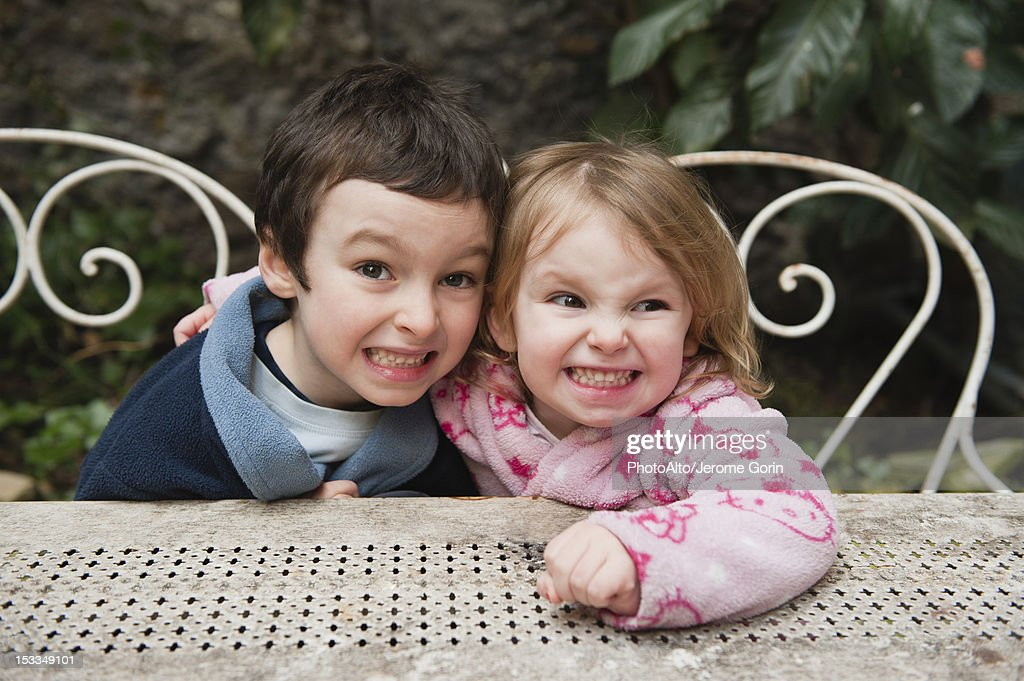 Young brother and sister smiling together outdoors, portrait : Stock Photo