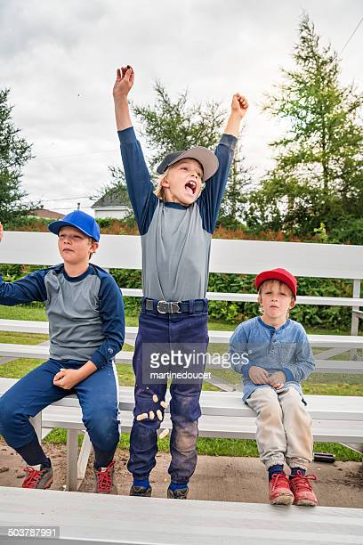 Young brothers cheering and eating peanuts watching baseball game outdoors.