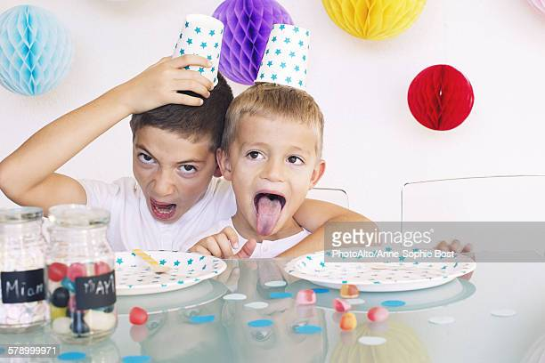 Young brothers making faces during a birthday party
