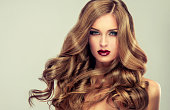 Young, brown haired woman  with voluminous hair. Beautiful model with long, dense and curly hairstyle, vivid make-up and red lipstick on the lips. Perfect hair curls and sexy look.Incredibly dense, wa