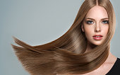 Young, brown haired woman  with straight and voluminous hair. Beautiful model with long, dense straight hairstyle and vivid make-up. Perfect flying hair and sexy look.Incredibly dense and shiny hair.