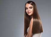 Young and pretty woman with soft smile on the face in demonstrating perfectly looking, dense and straight shiny hair. Natural gloss of healthy hair. Hair care and hairdressing art.
