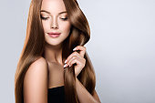 Young, brown haired woman  with voluminous hair.Beautiful model with long, dense, straight hairstyle and vivid makeup, is touching own hair with tenderness. Symbol of attentiveness to hair and good ca