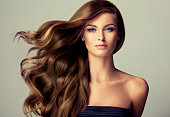 Young, brown haired woman  with voluminous hair. Beautiful model with long, dense and curly hairstyle and vivid make-up. Perfect hair curls and sexy look.Incredibly dense, wavy,and shiny hair.