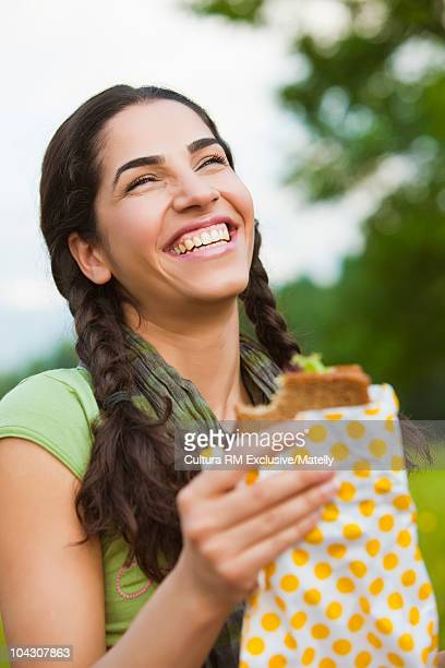 Young brown haired girl eating sandwich