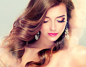 Young, brown haired woman  with voluminous, shiny and wavy hair. Beautiful model with long, dense and curly hairstyle, vivid make-up, rose lipstick on the lips and big jewelry earrings.