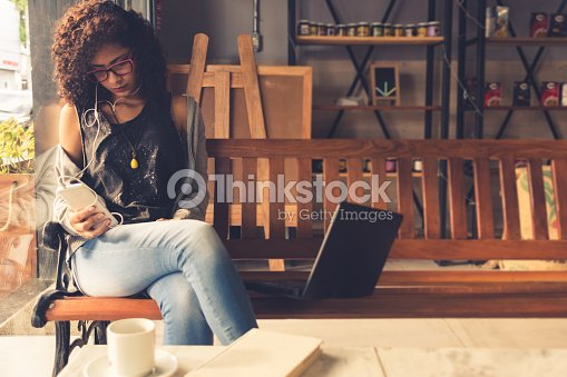 Young brunette curly hair woman at a coffee shop typing on a smart phone : Stock Photo