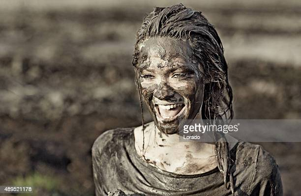 Young brunette female laughing during a mud run