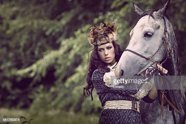 Young brunette female posing with horse
