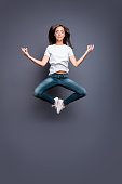Young brunette female practicing yoga levitate at the air. Calm girl jumping up in a position of meditation isolated on gray background
