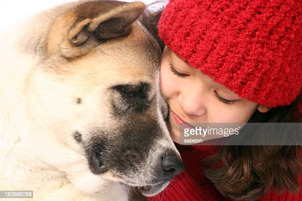 Young brunette girl wearing red beanie hugging brown dog