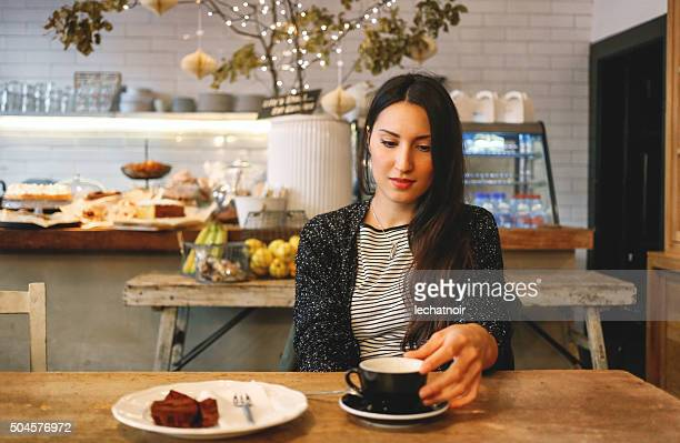 Young brunette having a coffee and a chocolate cake