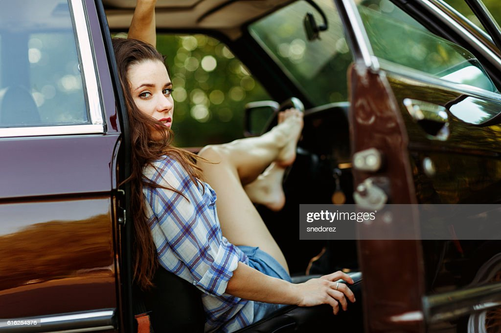 Young brunette in burgundy car , tinted photo : Foto de stock