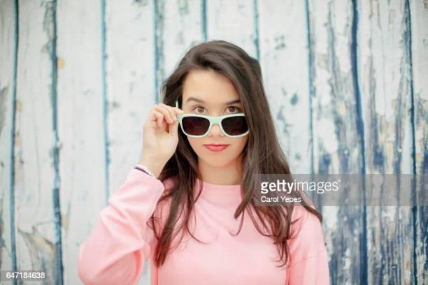 young brunette peeking over sunglasses