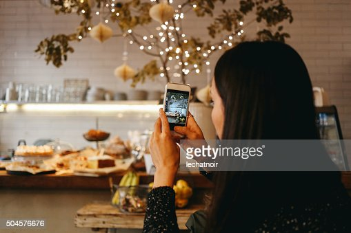 Young brunette taking a photo with a smartphone