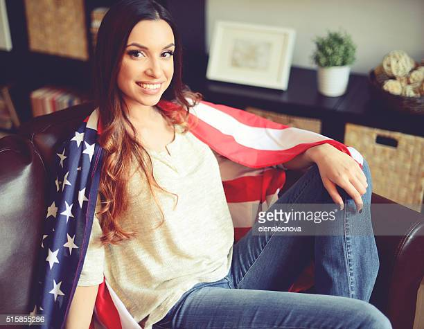 young brunette woman in home interior with American flag
