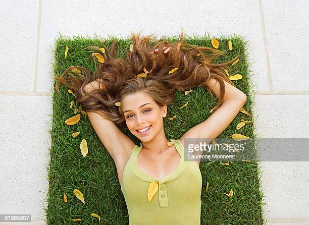 Young brunette woman relaxing on a grass square