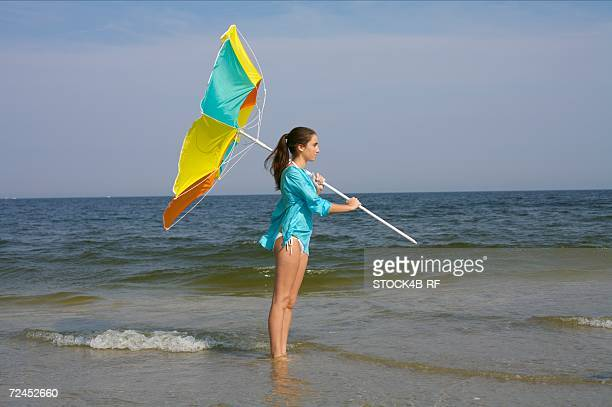 Young brunette woman standing in the shallow water of the sea with a sunshade in her hand