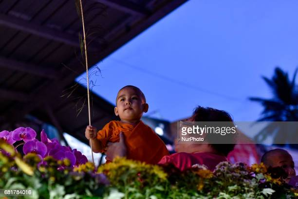 Young Buddhist monk and devotee take part in parade during Vesak day celebration in Kuala Lumpur Malaysia on May 10 2017 Vesak day on the fullmoon...
