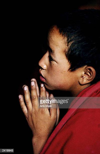 A young Buddhist monk cloaked in his saffron robe prays in the Thiksey monastery about 18 kilometers from Leh the capital of Ladakh India August 21...