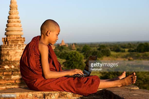Young Buddhist monk using laptop, Bagan