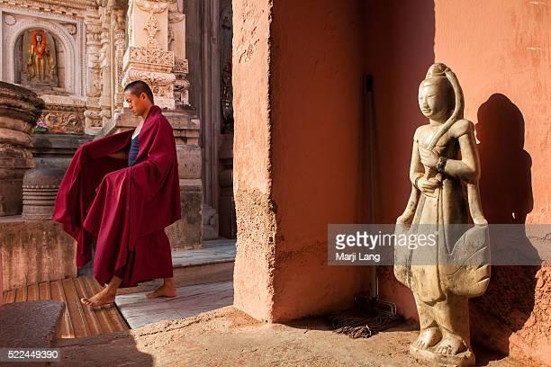 BODHGAYA BIHAR INDIA BODHGAYA BIHAR INDIA Young Buddhist monk walking by a Buddha statue in Mahabodhi temple Bodhgaya Bihar India The Mahabodhi...