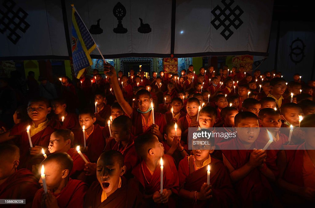 Young Buddhist Monks chant as they hold lighted candles during a rally at Tergar Monastry in Bodhgaya on December 30, 2012, following the cremation of a gangrape victim. The victim of a gang-rape and murder which triggered an outpouring of grief and revulsion across India was cremated at a private ceremony as it emerged she was planning to marry in February. The unidentified 23-year-old, the focus of nationwide protests since she was attacked on a bus in New Delhi two weeks ago, was cremated at a ceremony kept secret by authorities only hours after her body was repatriated from Singapore.