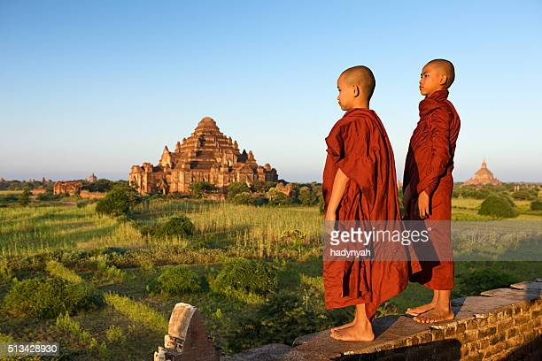 Young Buddhist monks looking at the sunset