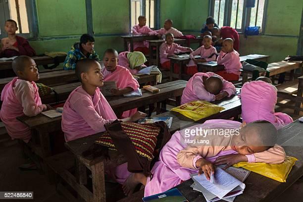 MANDALAY MYANMAR SAGAING MANDALAY MYANMAR Young Buddhist novice nuns reading sleeping and chatting in the classroom of their school in Sagaing near...