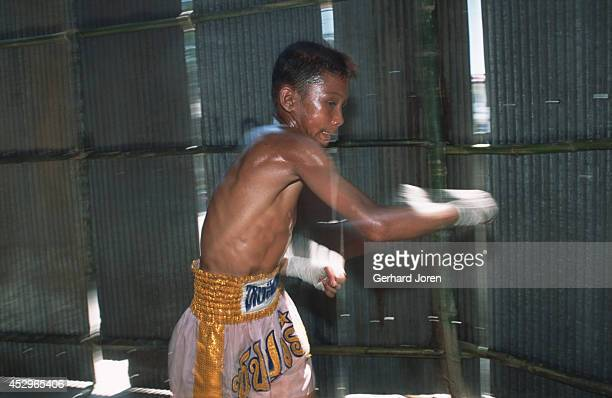 A young Burmese boxer gets warmed up with some shadow boxing before a fight in a shack at the ThaiBurmese border in Mae Sot Adult bouts have five...