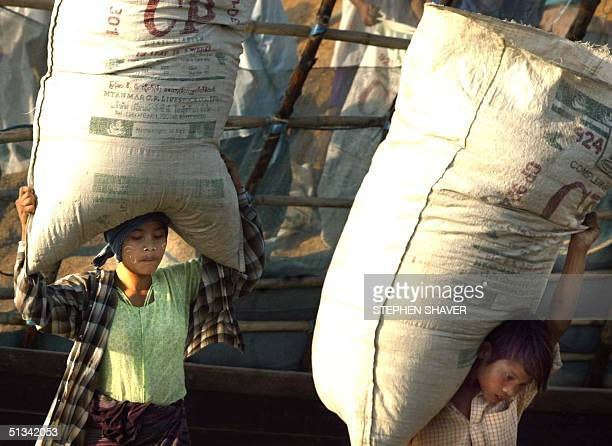Young Burmese children carry large sacks of wheat husks off a river barge as other children wait their turn at a makeshift dock in Yangon the capital...
