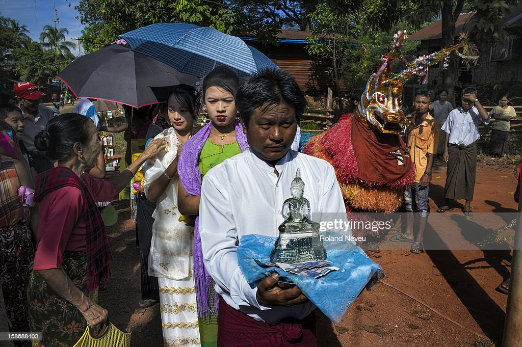 Young Burmese ladies leading the parade of citizen at a neighborhood in Moulmein who have organized a day of festivities to raise money for construction work to be done at their pagoda..