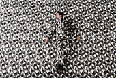 Young busienss man wearing patterned suit blending into background, elevated view