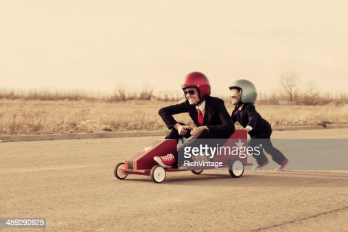 Young Business Boy Pushes Woman in Toy Car