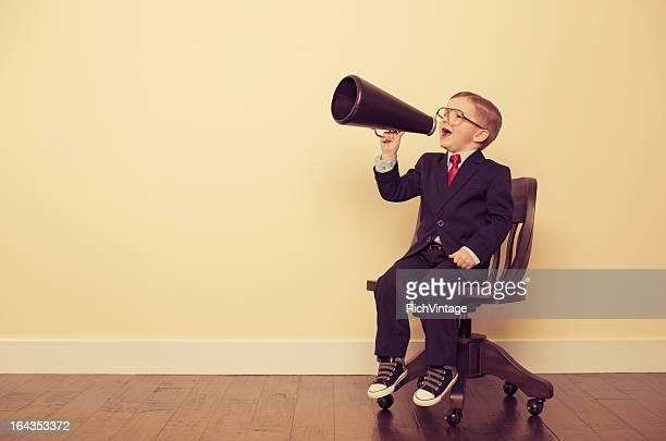 Business giovane ragazzo seduto in poltrona urla attraverso Megafono