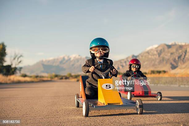 Young Business Boys in Suits Race Toy Cars