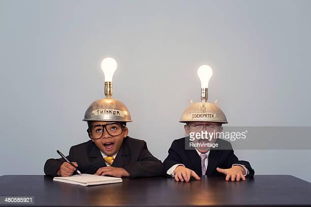 Jeune garçon portant costume d'affaires pensant et des casquettes