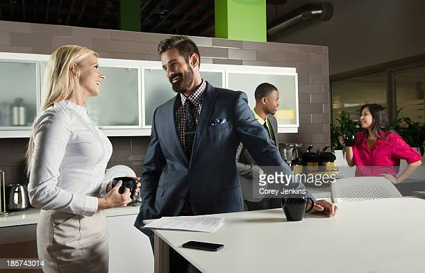Young business colleagues chatting in office kitchen
