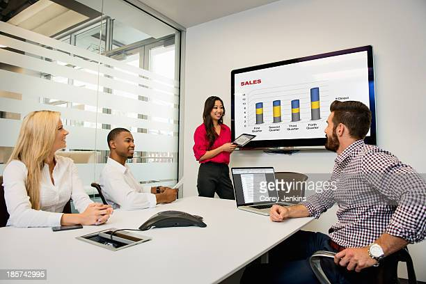 Young business colleagues looking at digital table in meeting in conference room