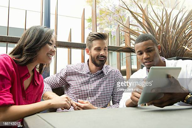 Young business colleagues looking at digital tablet in meeting