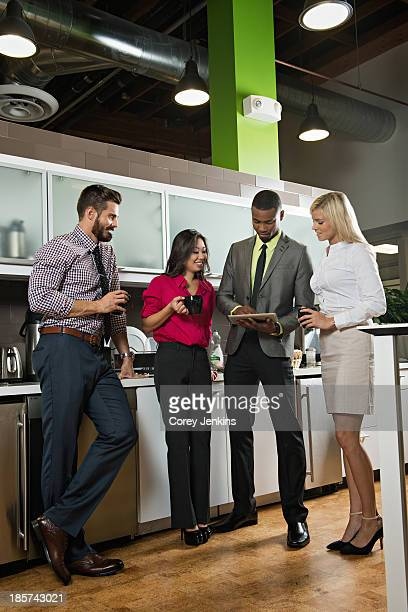 Young business colleagues looking at digital tablet office kitchen