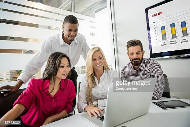 Young business colleagues looking at laptop in conference room