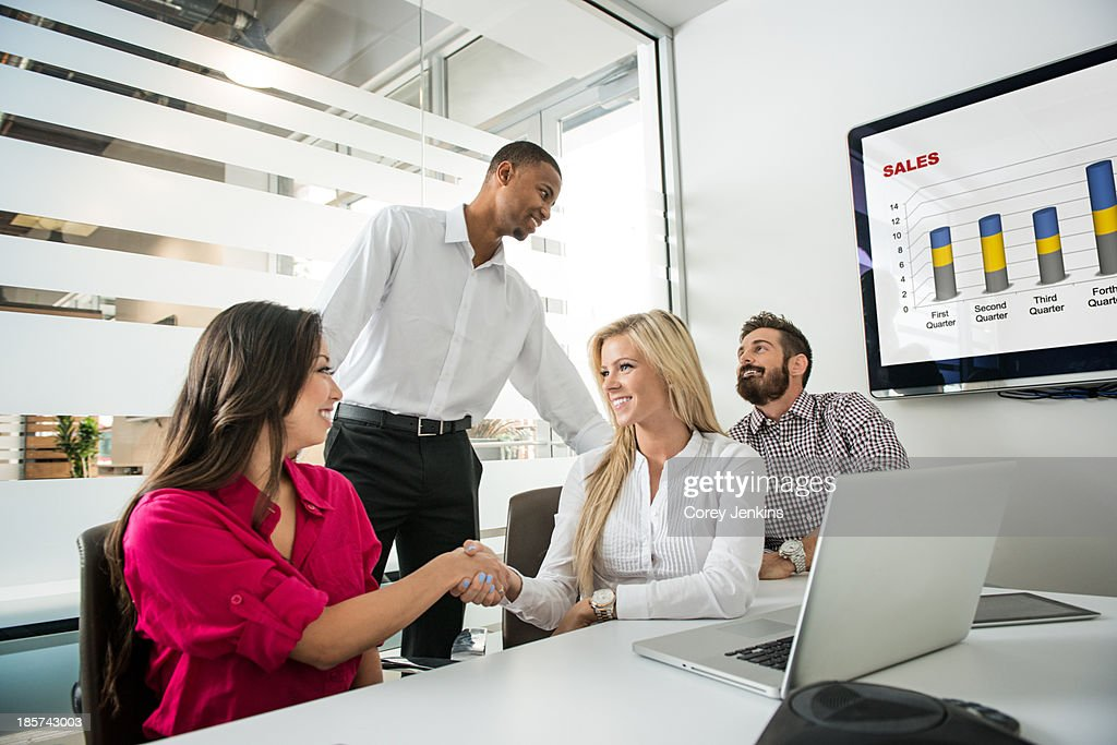Young business colleagues shaking hands in conference room : Stock Photo